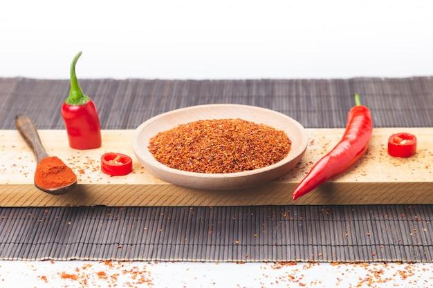 Pimenta vermelha cortada e pimenta em pó espalhada na base de madeira. gastronomia e condimentos culinários.
