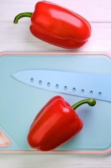 Pimenta vermelha doce e uma faca em uma tábua, em uma superfície de madeira branca