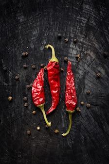 Pimenta vermelha e pimenta preta em uma mesa de madeira escura