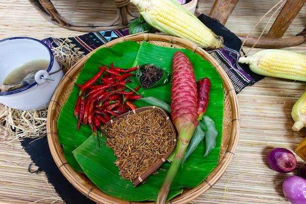 Pimenta vermelha e sementes de arroz com milho na cesta de bambu