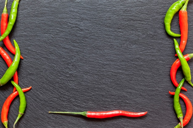 Pimenta vermelha e verde picante fresca em uma placa de ardósia, várias pimentas coloridas e pimenta caiena em um fundo escuro de cima. vista superior, copie o espaço.