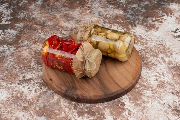 Pimenta vermelha em conserva e cogumelos em uma jarra de vidro na placa de madeira.