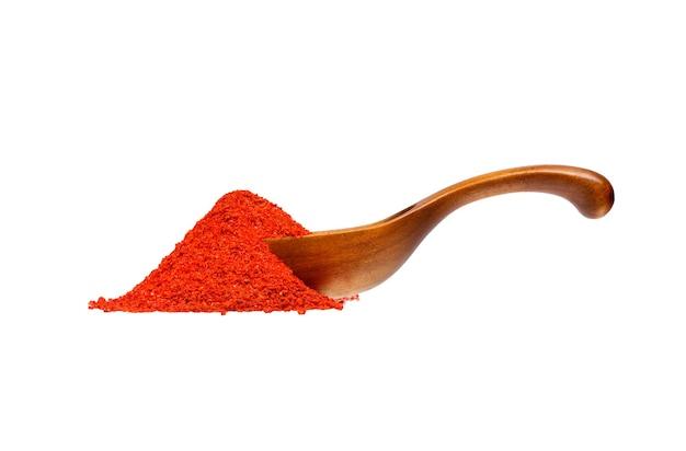 Pimenta vermelha em pó de pimienta roja na colher de pau, isolada no fundo branco.