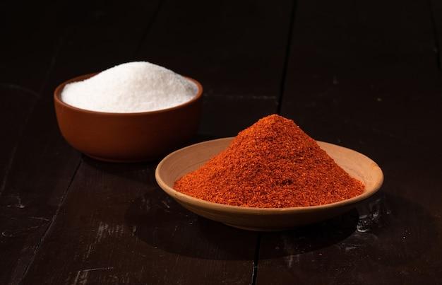 Pimenta vermelha em pó e sal em pó são especiarias indianas e ingredientes alimentares indianos em madeira