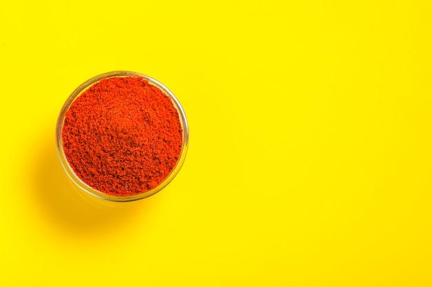 Pimenta vermelha em pó em uma tigela de vidro na superfície amarela