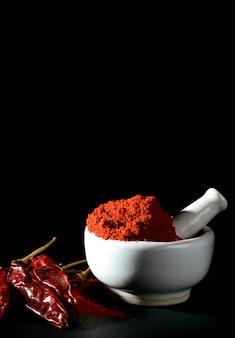 Pimenta vermelha em pó no pilão com almofariz e pimentão vermelho.