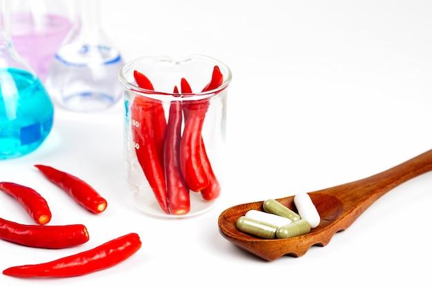 Pimenta vermelha em um copo com fita métrica com remédio em uma colher de pau Foto Premium
