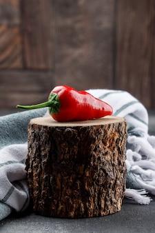 Pimenta vermelha em um pedaço de madeira com vista lateral para pano de piquenique na parede de azulejos cinza e pedra