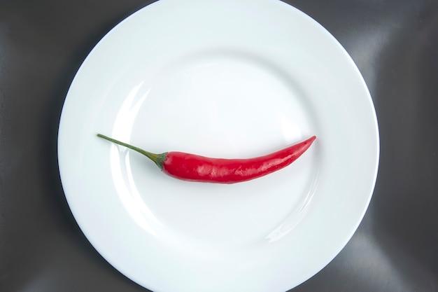Pimenta vermelha em um prato branco, especiarias e alimento vegetativo