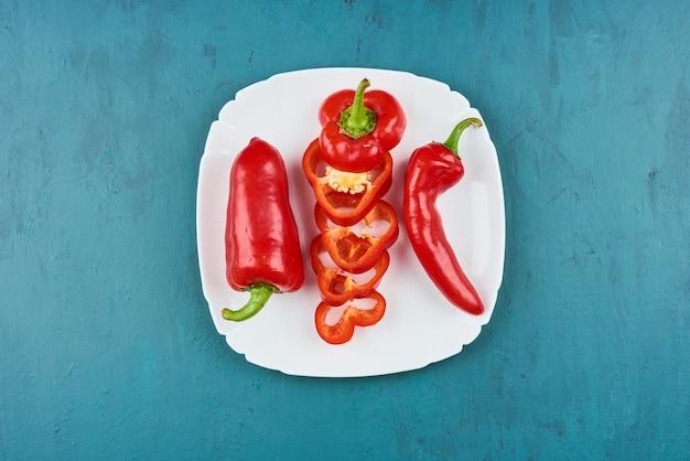 Pimenta vermelha em um prato branco, vista superior.