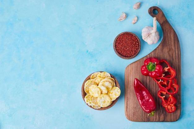 Pimenta vermelha fatiada e pimentão em uma bandeja de madeira servida com batatas fritas, vista superior.