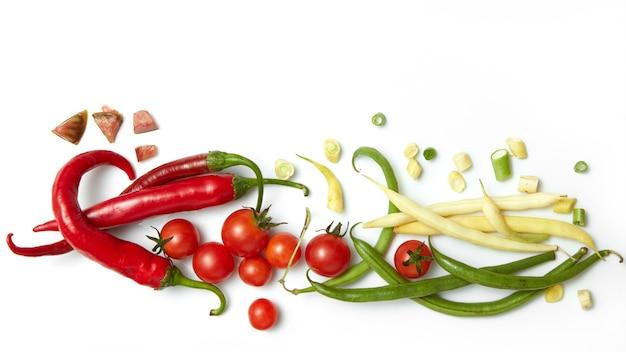 Pimenta vermelha, feijão amarelo e verde com tomate cereja. isolado em uma mesa branca.