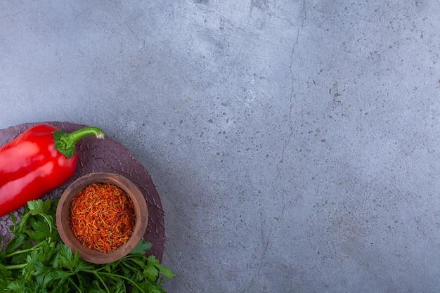 Pimenta vermelha, folhas de salsa e tomate cereja na peça de madeira.