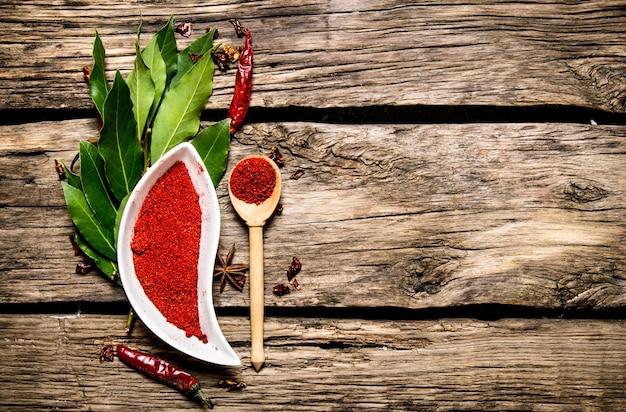 Pimenta vermelha moída e folhas de louro. em fundo de madeira. espaço livre para texto. vista do topo