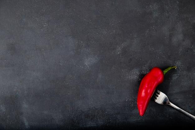 Pimenta vermelha no garfo no lado direito e mesa preta