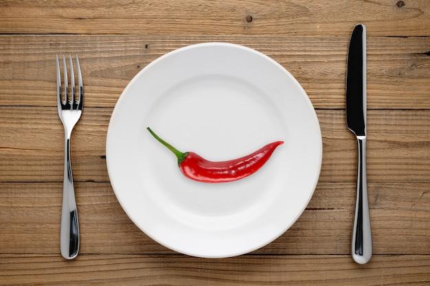 Pimenta vermelha no prato, garfo e faca na madeira