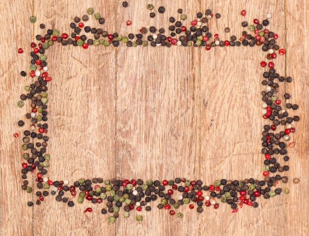 Pimenta vermelha, preta e verde na mesa de madeira