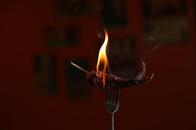 Pimenta vermelha queimando no garfo