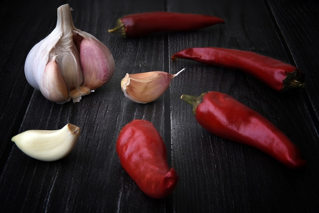 Pimenta vermelha quente com alho na mesa de madeira preta