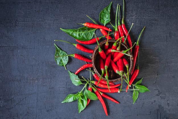 Pimenta vermelha quente no chão de madeira preto