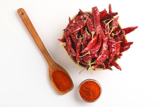 Pimenta vermelha seca e pimenta vermelha em pó em uma tigela de vidro e uma colher de pau na superfície branca