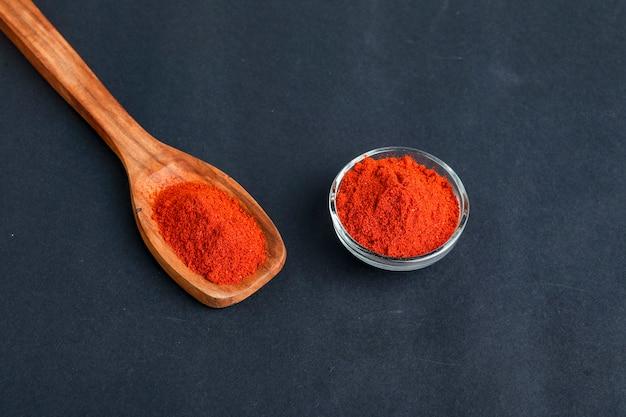 Pimenta vermelha seca e pó em uma tigela de vidro e uma colher de pau na superfície escura