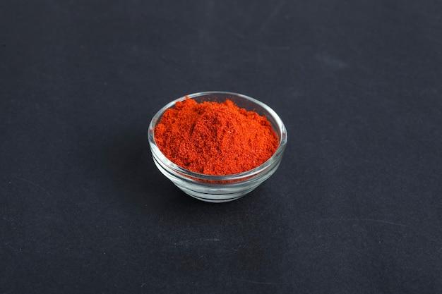Pimenta vermelha seca e pó em uma tigela de vidro na superfície escura