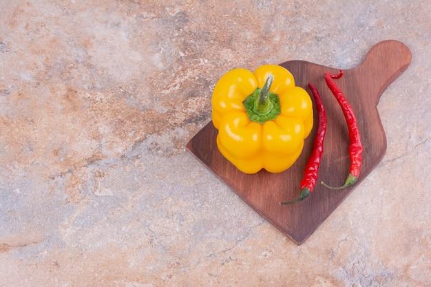 Pimentão amarelo com pimenta vermelha em uma travessa de madeira