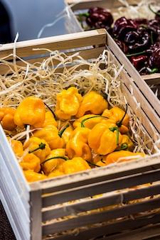 Pimentão amarelo e marrom estão em caixas de madeira. vendendo legumes no mercado