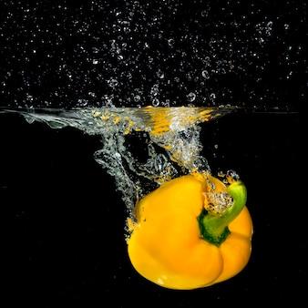 Pimentão amarelo fresco cair na água com um respingo e bolha de ar