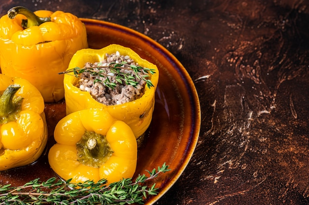 Pimentão amarelo recheado com carne, arroz e legumes. fundo escuro. vista do topo. copie o espaço.