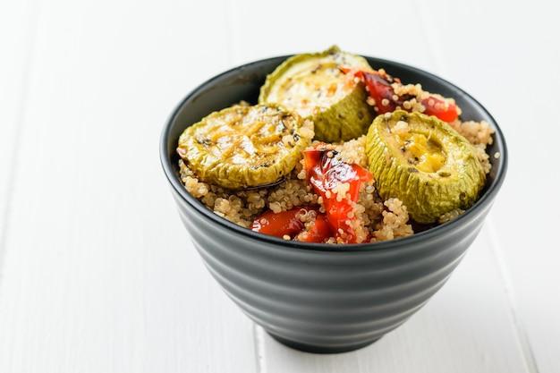 Pimentão assado, abobrinha e quinoa cozido em uma mesa branca. prato vegetariano.
