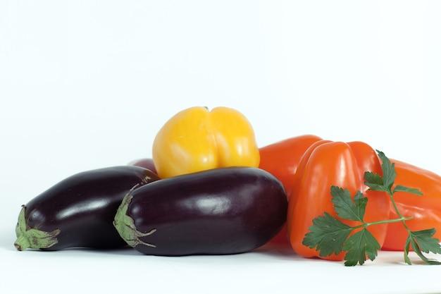 Pimentão, berinjela e raminhos de salsa em um fundo branco. foto com espaço de cópia
