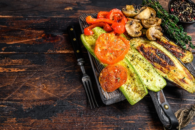 Pimentão de legumes grelhados, abobrinha, berinjela e tomate com ervas secas em uma placa de madeira. fundo de madeira escuro. vista do topo. copie o espaço.