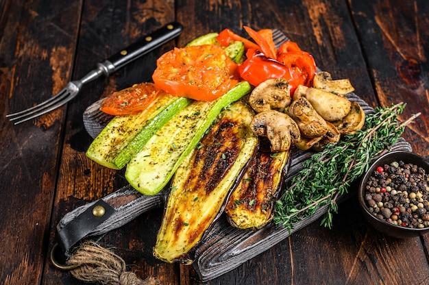 Pimentão de legumes grelhados, abobrinha, berinjela e tomate com ervas secas em uma placa de madeira. fundo de madeira escuro. vista do topo.