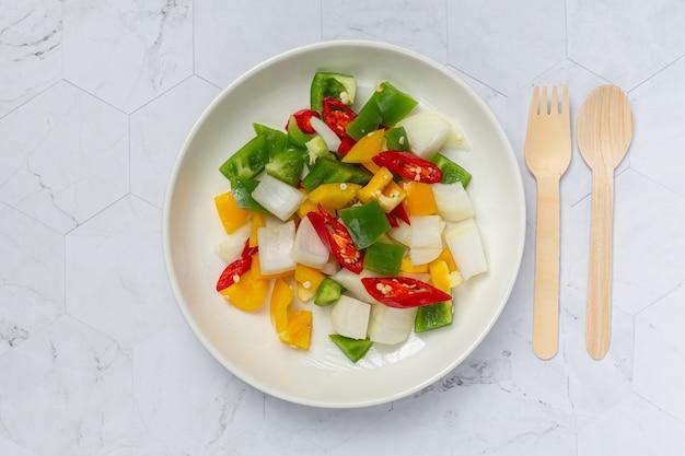 Pimentão doce fresco e cebola cortados em um prato branco