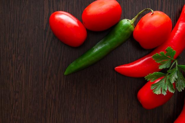 Pimentão e tomate em um fundo escuro de madeira