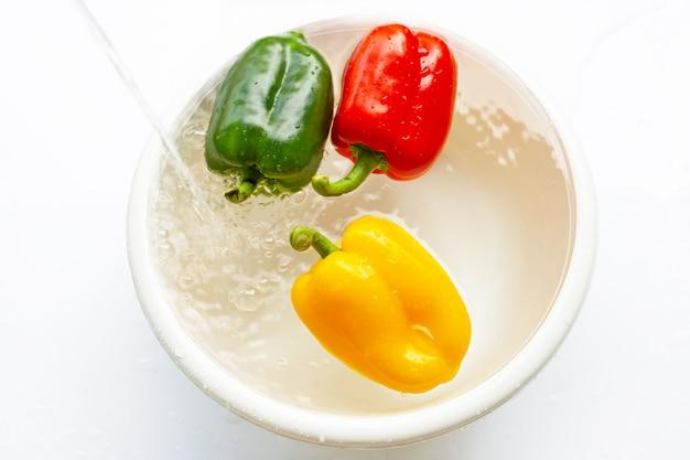 Pimentão embebido em água. legumes frescos de lavagem no fundo branco.