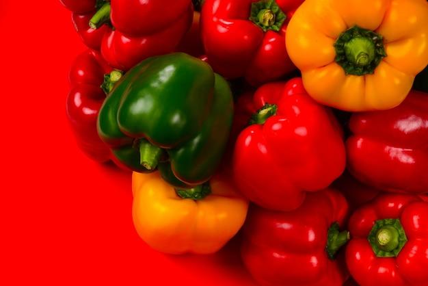 Pimentão fresco vermelho, amarelo e verde em uma superfície vermelha