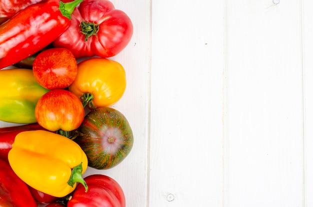 Pimentão multicolorido e tomate na mesa de madeira. foto do estúdio.