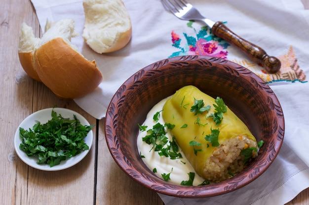 Pimentão recheado servido com creme azedo e pão, prato tradicional de diferentes nações.