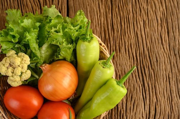Pimentão, tomate, cebola, salada e couve-flor em uma cesta de madeira e mesa de madeira.