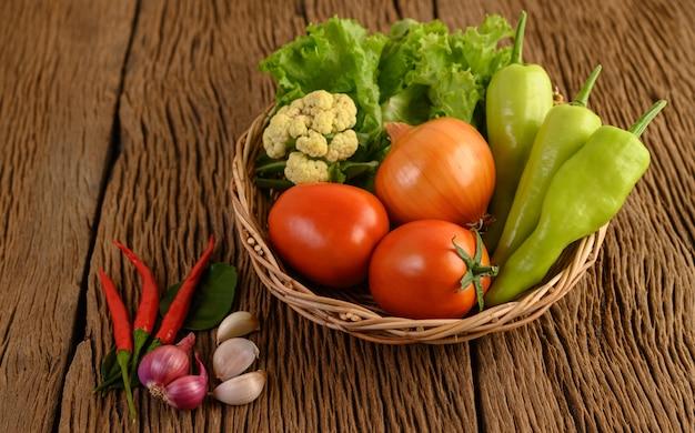 Pimentão, tomate, cebola, salada, pimentão, chalota, alho, couve-flor e kaffir limão folhas em uma cesta de madeira na mesa de madeira