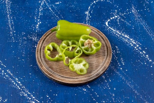 Pimentão verde e fatias na placa de madeira na mesa de mármore.