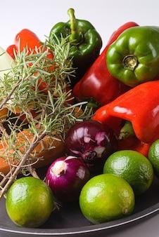 Pimentão verde e vermelho, cebola, limão, alecrim, ingredientes da receita em fundo branco.