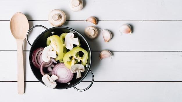 Pimentão verde fatiado; cogumelos e cebolas em cozinhar panela com dentes de alho e colher em pano de fundo de madeira