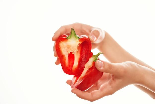 Pimentão vermelho na cozinha de mãos cozinhando fundo claro