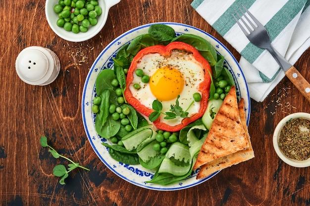 Pimentão vermelho recheado com ovos, folhas de espinafre, ervilhas e microgreens em um prato de café da manhã no fundo da velha mesa de madeira. vista do topo.