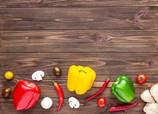 Pimentão vermelho, verde e amarelo, cogumelos e tomate cereja em fundo de madeira