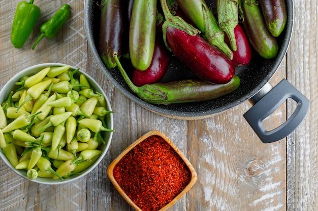 Pimentas com berinjela, flocos de pimenta vermelha em uma tigela de madeira,